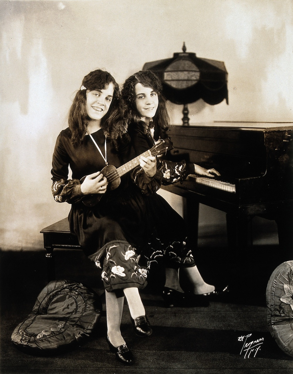 V0029601 Daisy and Violet Hilton, conjoined twins, playing piano and Credit: Wellcome Library, London. Wellcome Images images@wellcome.ac.uk http://wellcomeimages.org Daisy and Violet Hilton, conjoined twins, playing piano and ukelele. Photograph, c. 1927. 1930 Published:  -  Copyrighted work available under Creative Commons Attribution only licence CC BY 4.0 http://creativecommons.org/licenses/by/4.0/