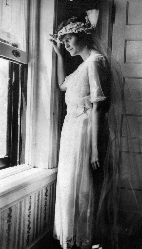 "EH5726P Hadley Richardson in her wedding dress looking out the window on her wedding day in Horton Bay, MI, 3 September 1921. Please credit: ""Ernest Hemingway Collection/John F. Kennedy Presidential Library and Museum, Boston."""
