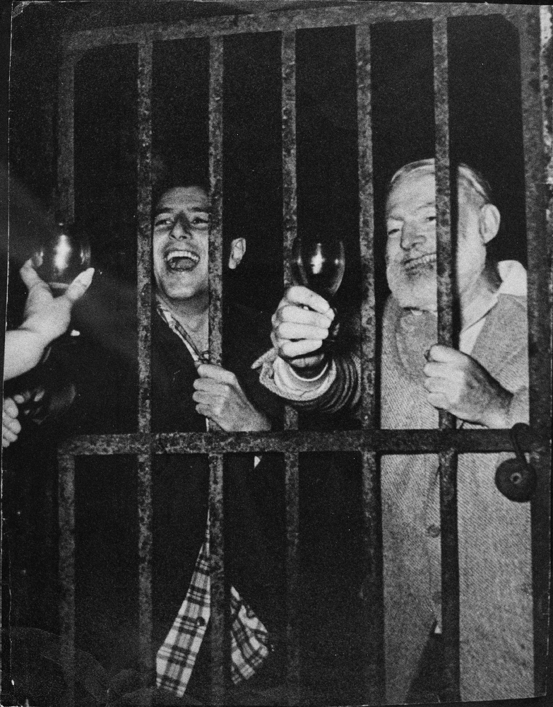 EH8969P  August 1959 Ernest Hemingway and Antonio Ordonez behind bars drinking and laughing.  Copyright unknown in the Ernest Hemingway Collection at the John F. Kennedy Presidential Library and Museum, Boston.