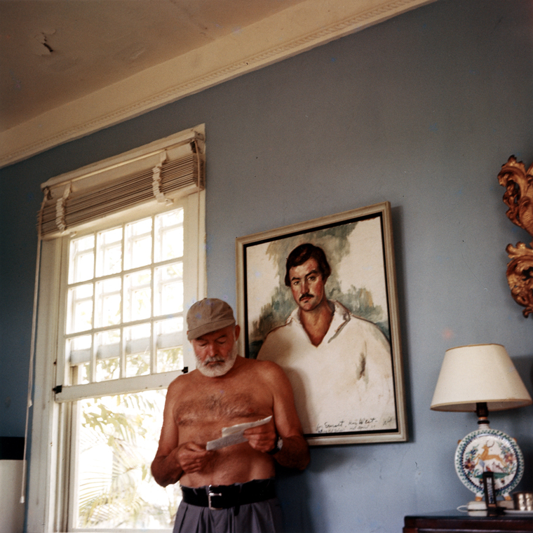 EH-C176T  Ernest Hemingway at his home in Cuba, circa 1953, standing in front of a 1929 portrait of himself by Waldo Pierce. Photograph in the Ernest Hemingway Photograph Collection, John F. Kennedy Presidential Library and Museum, Boston.