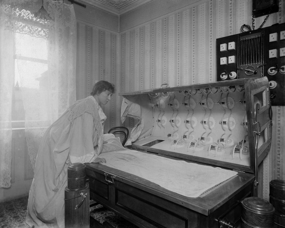 circa 1900: A woman inspects an Electric Bath at the Light Care Institute. The Electric Bath is probably a forerunner of the modern sunbed, although it was more likely used for medicinal reasons. (Photo by Reinhold Thiele/Thiele/Getty Images)