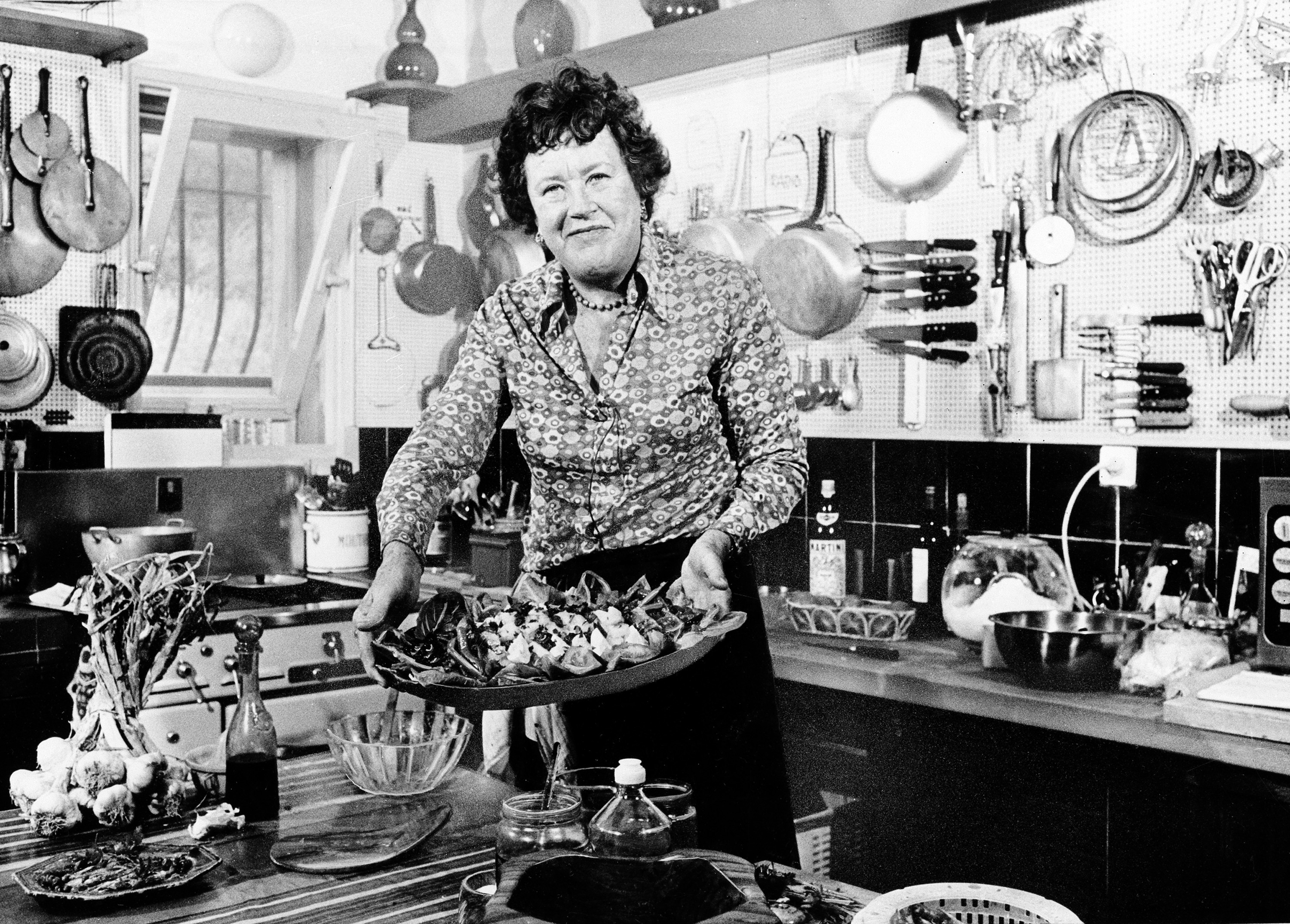 FILE - In this Aug. 21, 1978, file photo, American television chef Julia Child shows a salade nicoise she prepared in the kitchen of her vacation home in Grasse, southern France. Child changed the way Americans look at food as well as the way women looked at cooking and themselves. (AP Photo, File) 08092012xBRIEFING