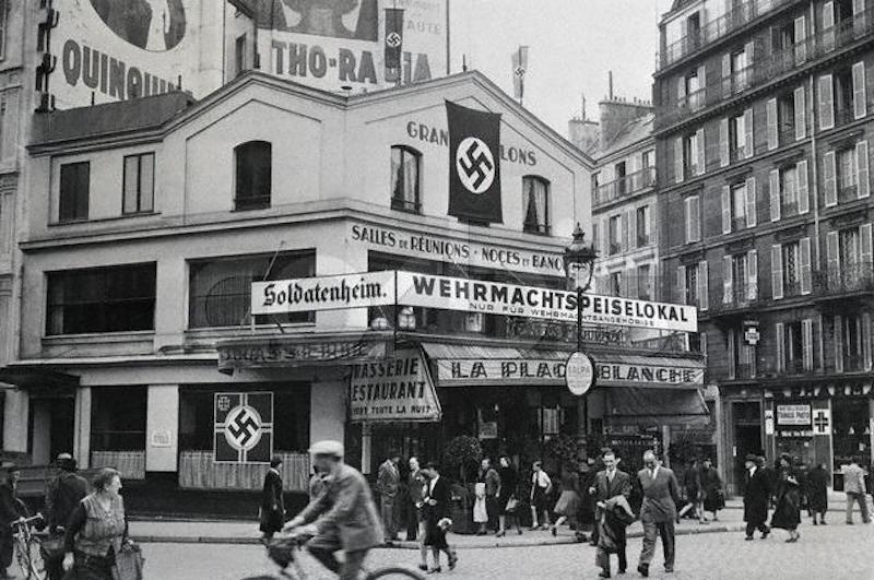 Nazi flags and German signs festoon La Place Blanche, the cafe across from the Moulin Rouge, in 1940. The cafe was reserved for exclusive use by occupying soldiers of the Wehrmacht. October 20, 1940 Paris, France