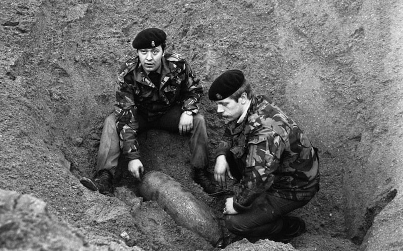 Workers inspecting an unexploded bomb from WW2 discovered next to the station