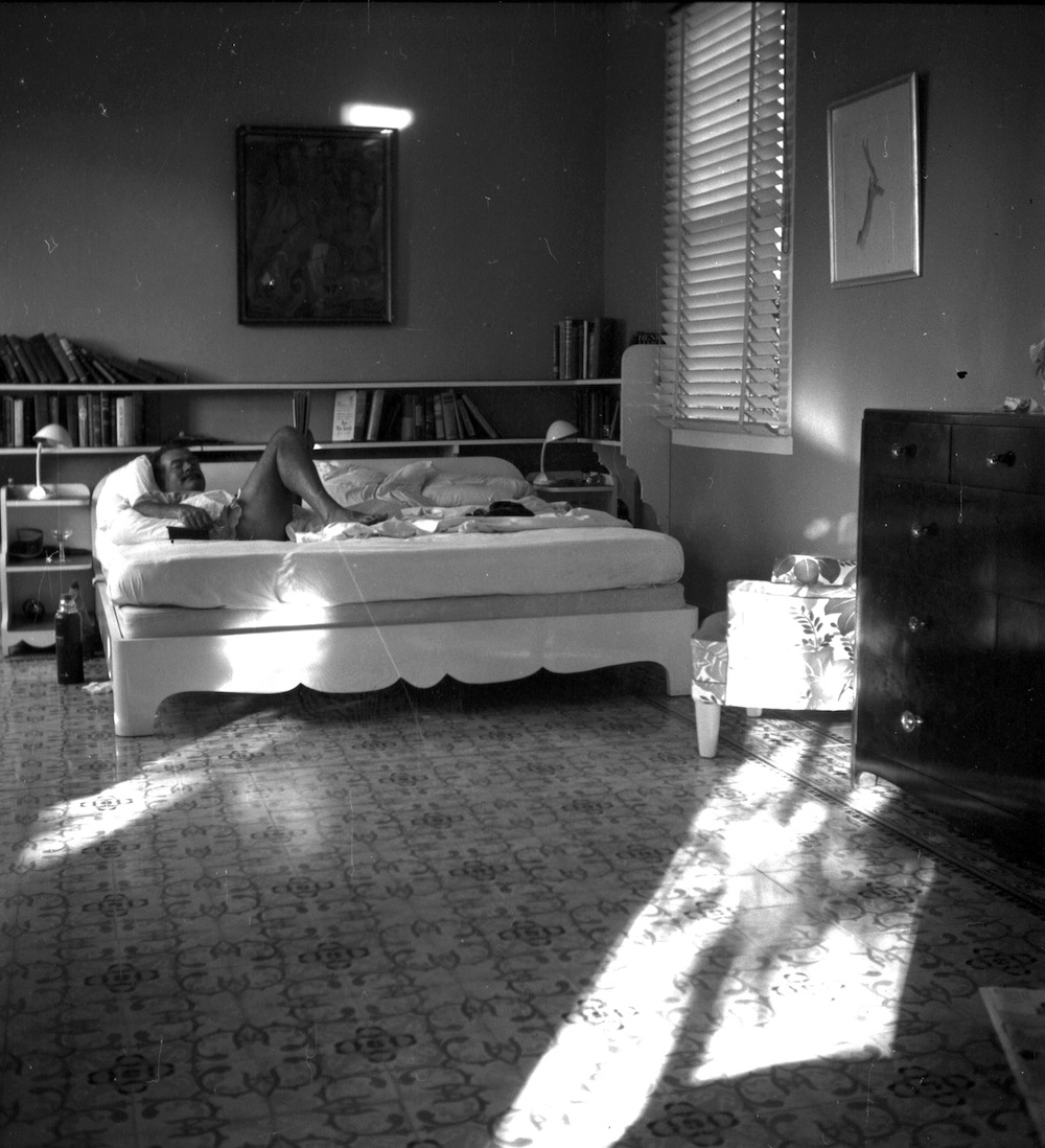 EH1963N nd. Ernest Hemingway lying on a bed in bedroom. Finca Vigia, Cuba. Please credit: Ernest Hemingway Collection at the John F. Kennedy Presidential Library and Museum, Boston.