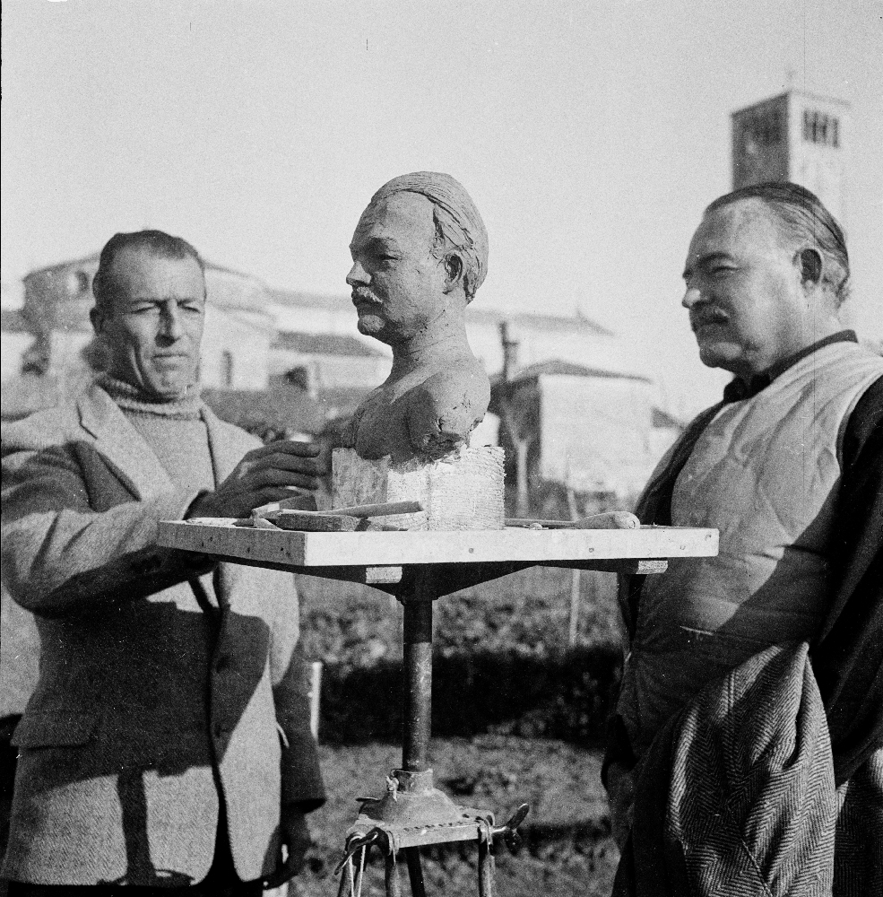 EH2812S December 1948 Ernest Hemingway with unidentified man and a sculpture of Hemingway's bust. Torcello Island, Venice, Italy. Copyright: Ernest Hemingway Collection at the John F. Kennedy Presidential Library and Museum, Boston.
