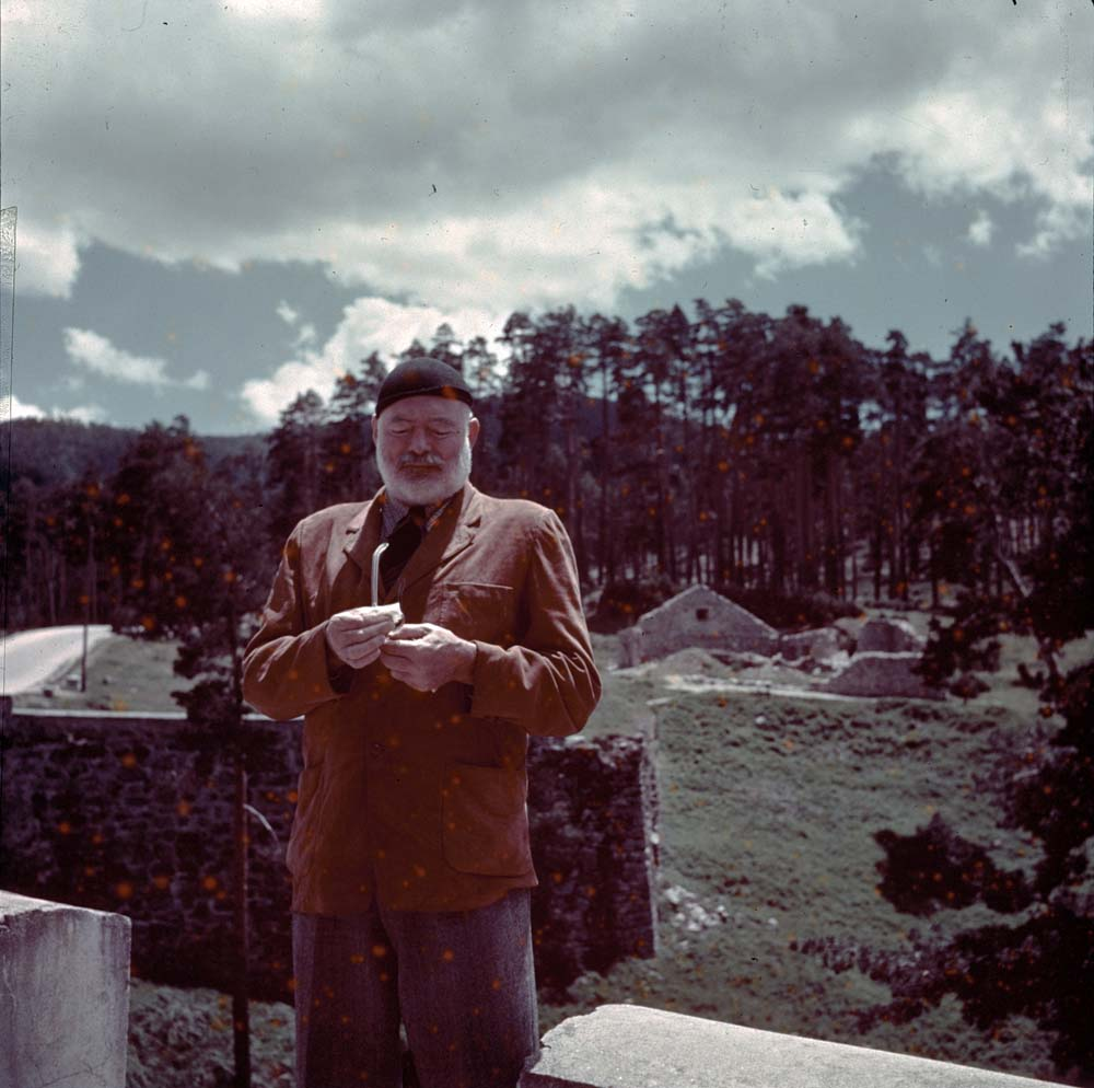 EH-C271T 1959/nd Ernest Hemingway cleans his glasses outdoors. Red spots original to transparency.