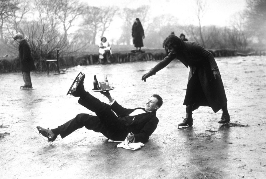 13th February 1936: A skating waiter slips on the ice, drinks tray in hand, but doesn't spill a drop! (Photo by E. Dean/Topical Press Agency/Getty Images)
