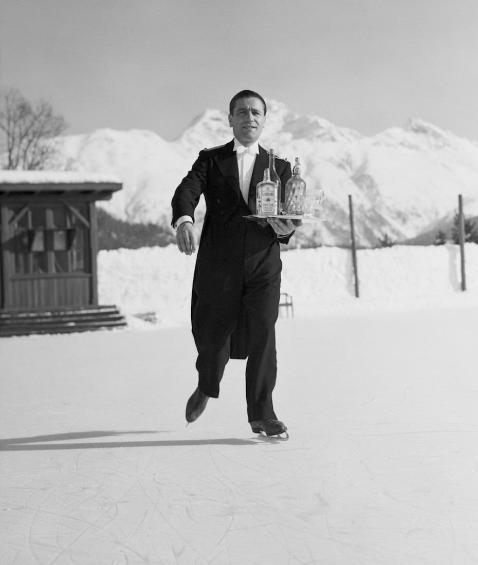 8th January 1938: A waiter skates across the ice at St. Moritz carrying a tray of drinks for his customers. (Photo by Horace Abrahams/Fox Photos/Getty Images)