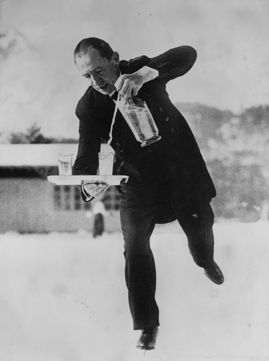 SWITZERLAND - JANUARY 01: Waiter on skates on skating rink, pouring soda water into a glass which he is balancing on a tray. Photography. Switzerland. St. Moritz. About 1935. (Photo by Imagno/Getty Images) [Kellner auf Schlittschuhen auf dem Eislaufplatz, aus einer Siphonflasche in ein Glas, das er auf dem Serviertablett balanciert, Sodawasser einschenkend. Photographie. Schweiz. St. Moritz. Um 1935.]