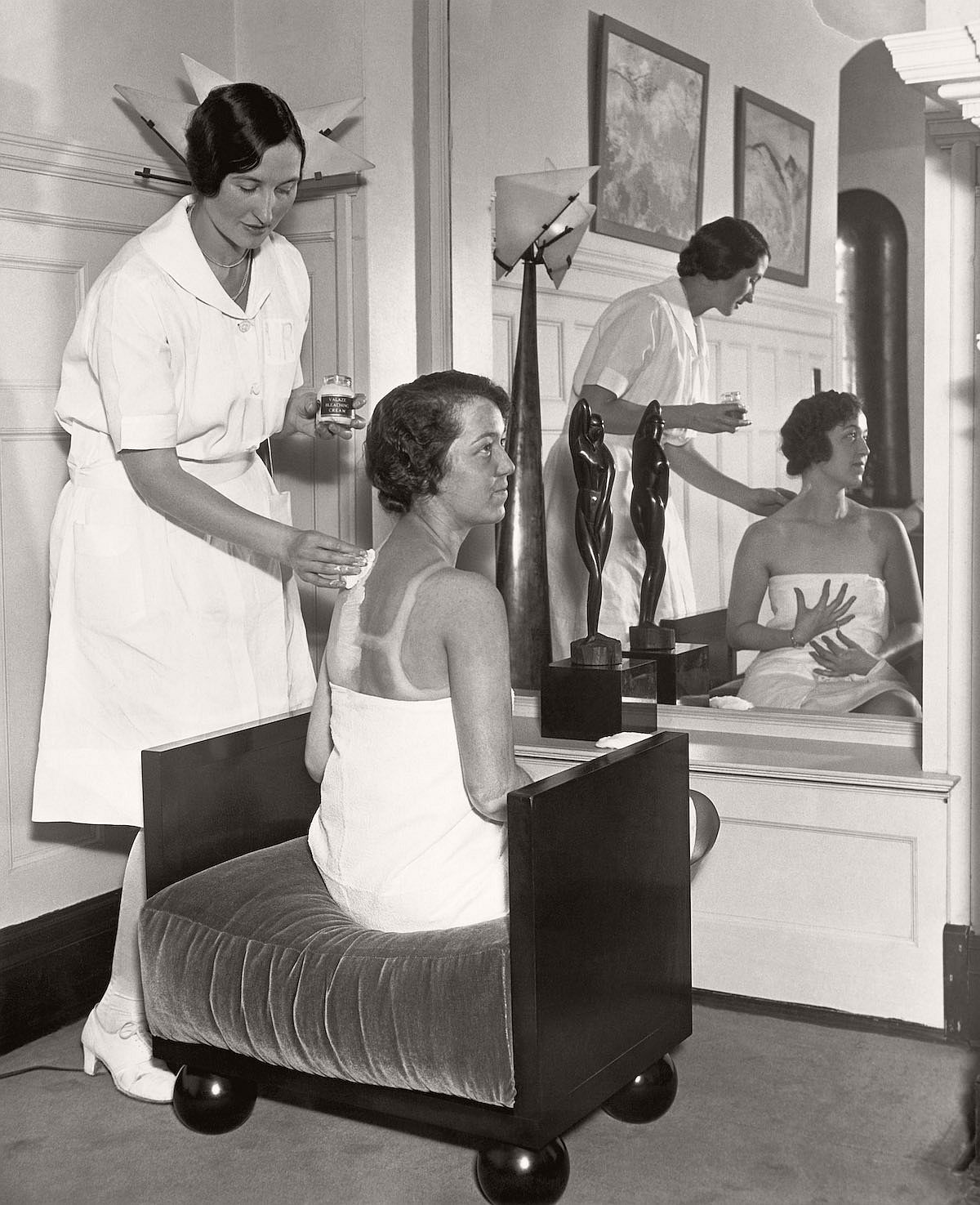 30 Sep 1929, Chicago, Illinois, USA --- In the fashionable Gold Coast salon of Helena Rubenstein, Carolyn Lang applies lotions to Billie Gloss' suntanned back, bleaching it down so that Miss Gloss will be the same pale shade all over. --- Image by © Underwood & Underwood/Corbis