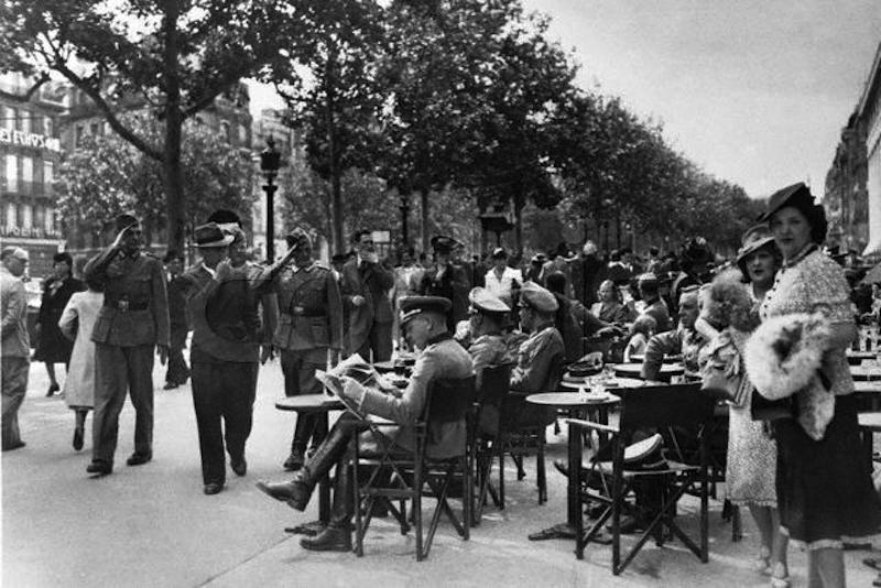 German officers and Parisians mingle near a sidewalk cafe on the Champs Elysees on Bastille Day in 1940. The German armed forces occupied France earlier that year. July 14, 1940 Champs Elysees, Paris, France